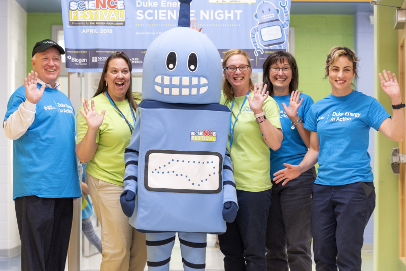 Teachers and volunteers pose with Kelvin the spokesbot at Lincoln Heights Elementary School