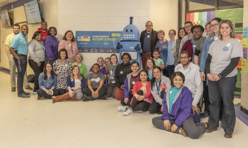 Teachers pose with Kelvin the spokesbot at Martin Millennium Academy