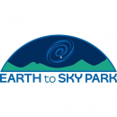 Earth to Sky Park Logo is a half dome shape, with green mountains at the base, and a dark blue sky above. There is a spiral share in the center representing a dark sky object like a galaxy.